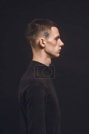 Young man with tattoo on temple isolated on black