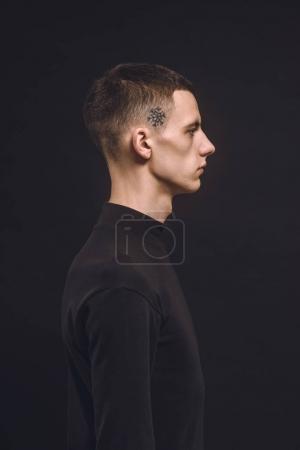 Jeune homme avec tatouage sur temple isolé sur fond noir