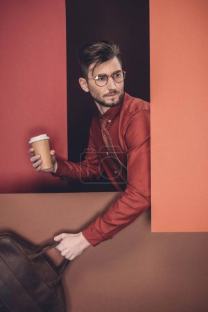 Businessman in glasses holding briefcase and paper cup by red paper walls isolated on black