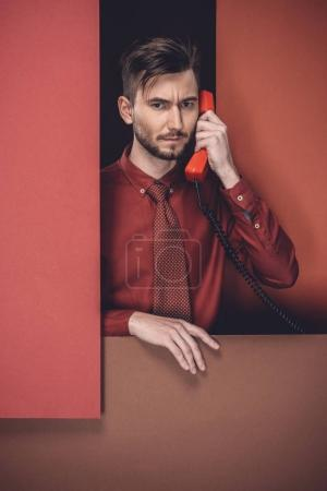 Thoughtful man holding phone headset by red paper walls isolated on black