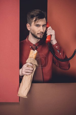 Thoughtful man holding baguette and phone headset by red paper walls isolated on black