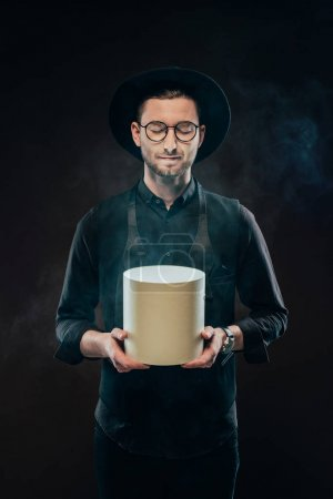 Young man with closed eyes holding carton box isolated on black