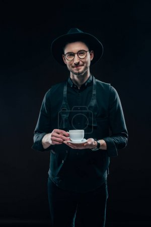 Smiling young man holding cup in hands isolated on black