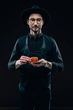 Stylish man holding cup with coffee isolated on black
