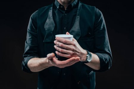 Close-up view of coffee cup in male hands isolated on black