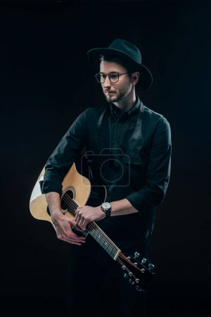 Young guitarist in black clothes holding acoustic guitar isolated on black