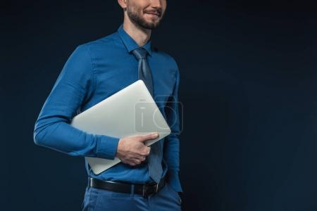 Young businessman holding laptop under arm isolated on blue