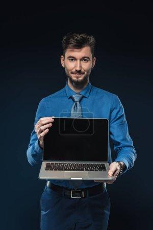 Photo pour Jeune homme d'affaires tenant un ordinateur portable avec écran blanc isolé sur bleu - image libre de droit