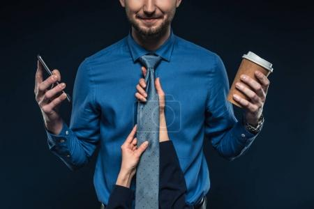 Female hands holding  tie of businessman with phone and coffee isolated on blue
