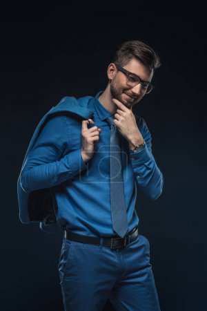 Smiling businessman in glasses holding his jacket isolated on blue