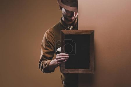 Stylish man in hat holding empty frame isolated on brown