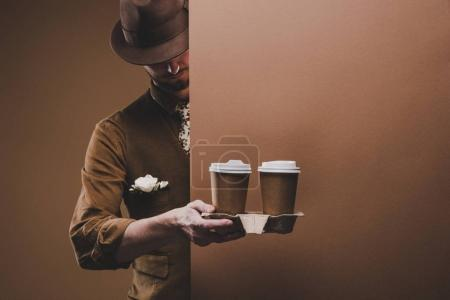Stylish man in casual clothes holding coffee in paper cups isolated on brown