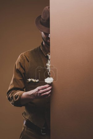 Man wearing corduroy vest and hat holding white rose isolated on brown
