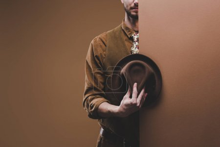 Stylish man wearing coat and holding hat isolated on brown