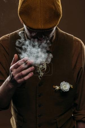 Man wearing corduroy vest and flat cap smoking isolated on brown
