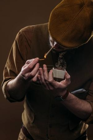 Man in stylish clothes lighting cigarette isolated on brown