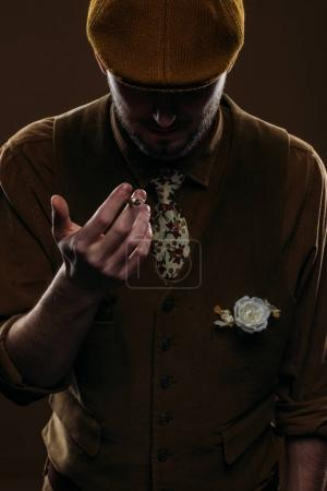 Young man in vintage styled clothes holding cigarette isolated on brown