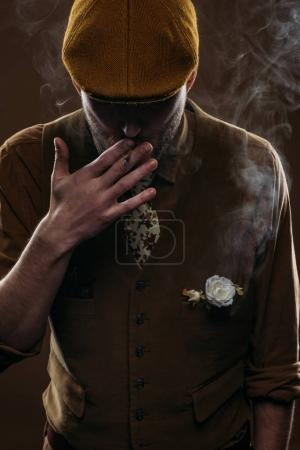 Stylish man in flat cap smoking cigarette isolated on brown