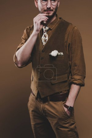 Man in stylish clothes holding toothpick in mouth isolated on brown