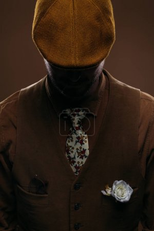 Man wearing corduroy vest and flat cap isolated on brown