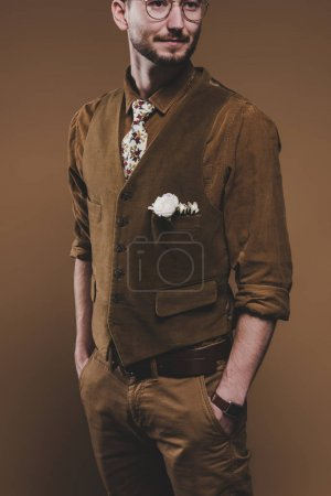 Young man in vintage styled clothes with boutonniere isolated on brown