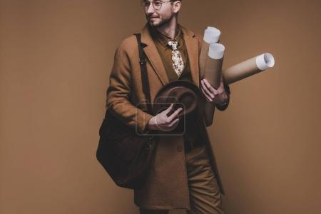 Young man in vintage styled clothes holding rolled papers isolated on brown