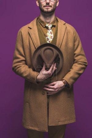 Photo pour Homme élégant au manteau avec chapeau en mains isolés sur violet - image libre de droit