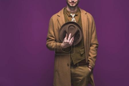 Stylish man wearing coat and holding hat isolated on purple