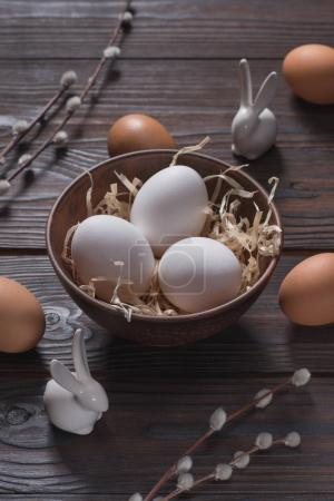 chicken eggs in bowl with straw and easter rabbits on wooden table