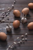 chicken eggs and easter rabbits on wooden surface