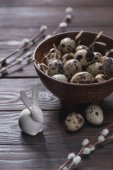 easter quail eggs in bowl with straw on table