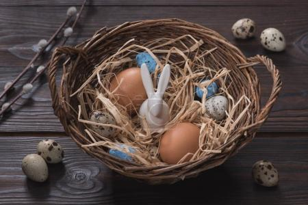 high angle view of chicken and quail easter eggs and rabbit in nest