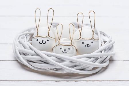 Photo pour Oeufs de poulet de Pâques avec des sourires et des oreilles de lapin dans le nid - image libre de droit
