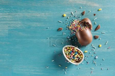 top view of broken chocolate easter eggs on wooden turquoise table