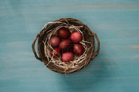 vue de dessus du panier de Pâques avec les oeufs peints et de la paille sur table