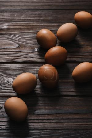 raw chiken eggs on wooden table