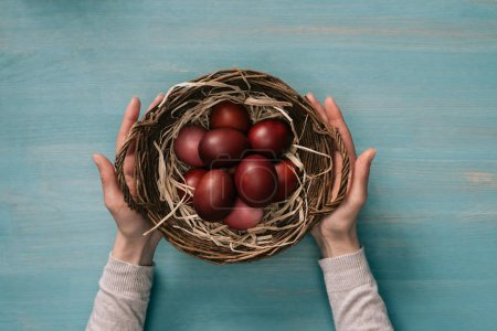 cropped image of woman holding easter basket with painted eggs
