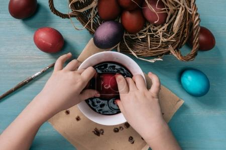cropped image of kid painting easter eggs in cup with paint at home