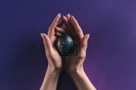 cropped image of woman holding painted easter egg above violet surface