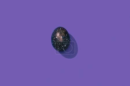 top view of one painted easter egg on violet surface