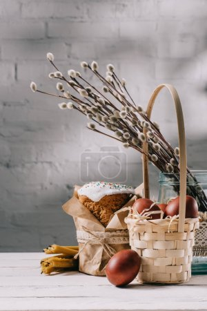 easter bread, easter chicken eggs and candles on wooden table