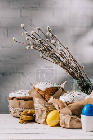 easter bread, painted chicken eggs and candles on wooden table