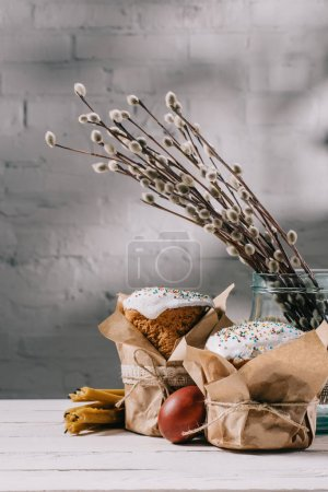 easter bread, catkins in jar and candles on wooden table