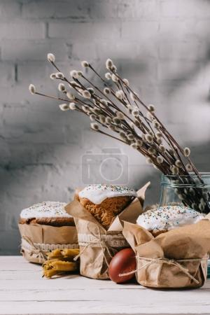 easter bread, painted egg and candles on wooden table