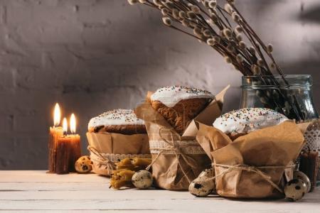 Photo pour Pain de Pâques, oeufs de caille et bougies sur table en bois - image libre de droit
