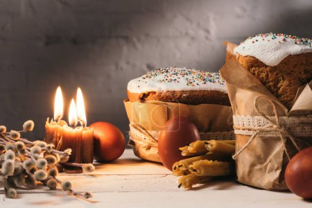 easter bread, painted eggs and candles on table