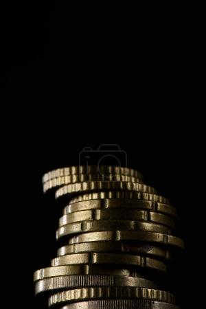 close up view of pile of coins isolated on black
