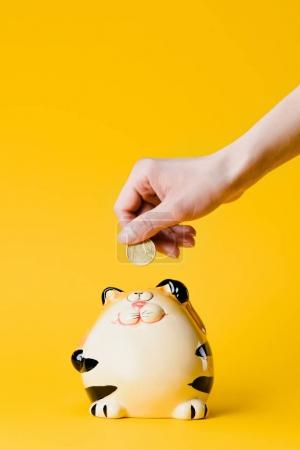 Photo for Cropped shot of woman putting 50 euro cent into still bank isolated on yellow - Royalty Free Image