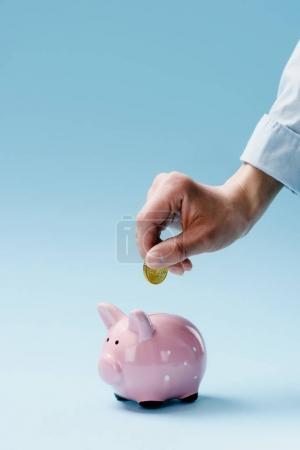 Foto de Vista parcial del hombre poniendo moneda en la alcancía rosa aislado en azul - Imagen libre de derechos