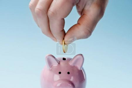 Photo for Partial view of man putting coin into pink piggy bank isolated on blue - Royalty Free Image